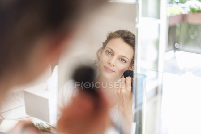 Femme regardant miroir maquillage yeux — Photo de stock