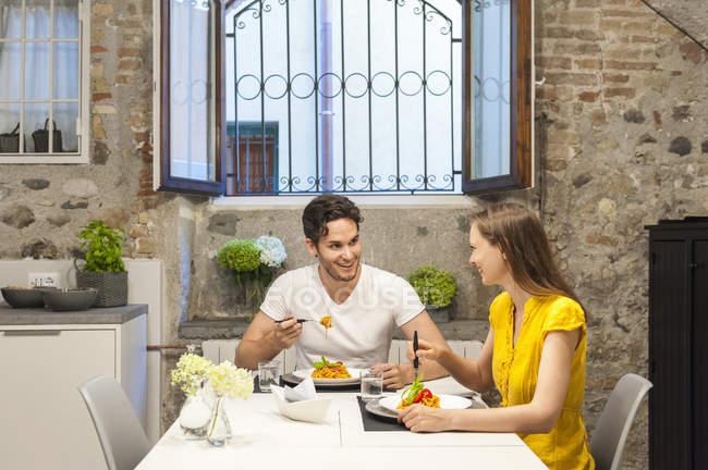 Пара на кухне ест макароны — стоковое фото