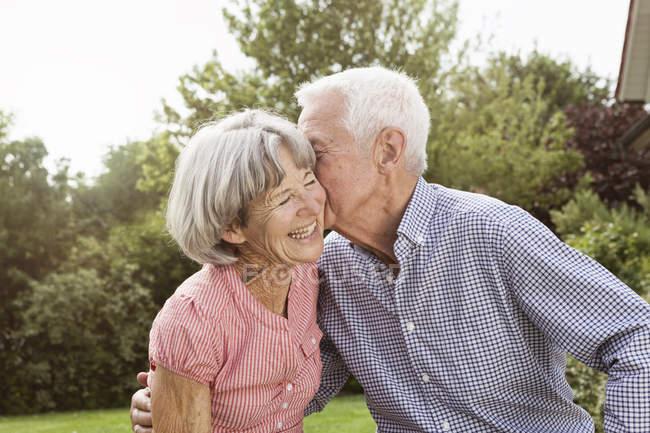 Felice coppia anziana baciare in giardino — Foto stock