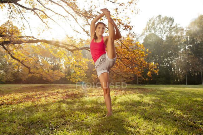 Woman holding a tai chi pose in autumnal park — Stock Photo