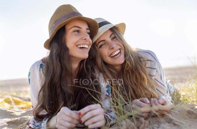 Retrato de dois melhores amigos com chapéus de verão deitados na praia — Fotografia de Stock