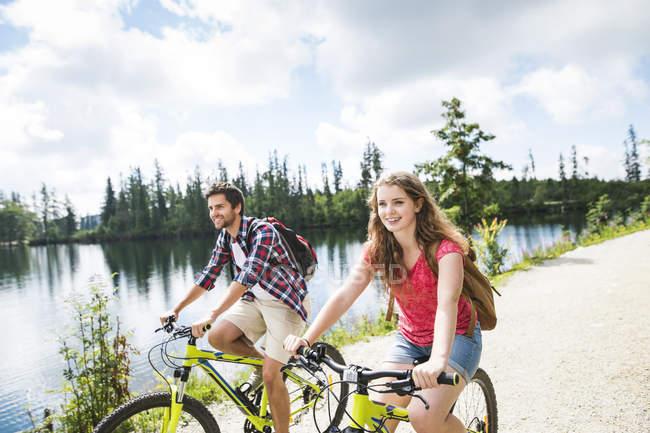Jovem casal andar de bicicleta na natureza — Fotografia de Stock