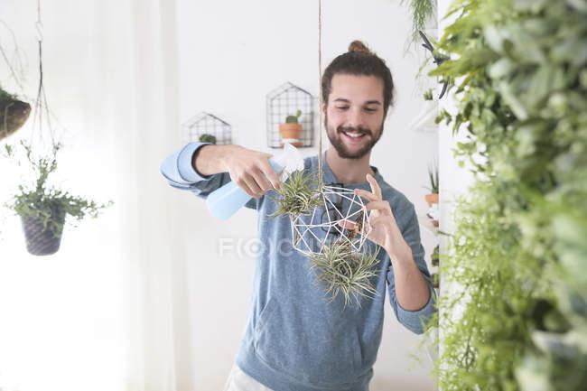 Молодой человек полива растений воздуха в геометрических Кулон — стоковое фото