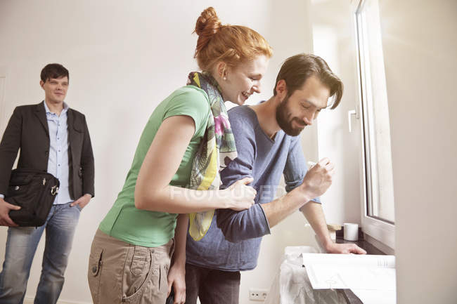 Happy couple signing contract in new apartment with real estate agent in background — Stock Photo