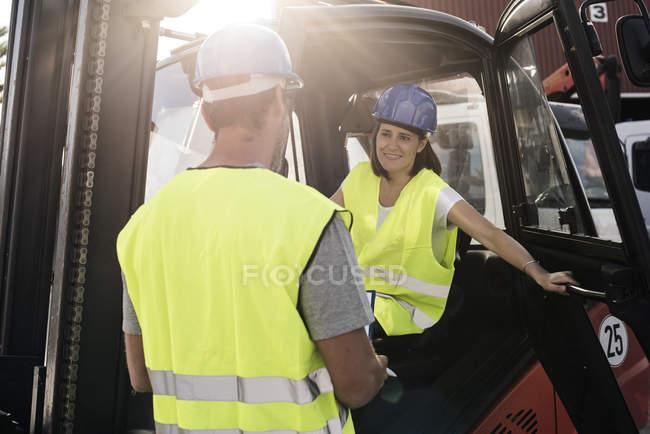 Жінка в навантажувача розмовляти з Форман — стокове фото