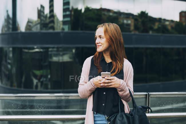 Souriant jeune femme debout avec téléphone portable et regardant de côté — Photo de stock