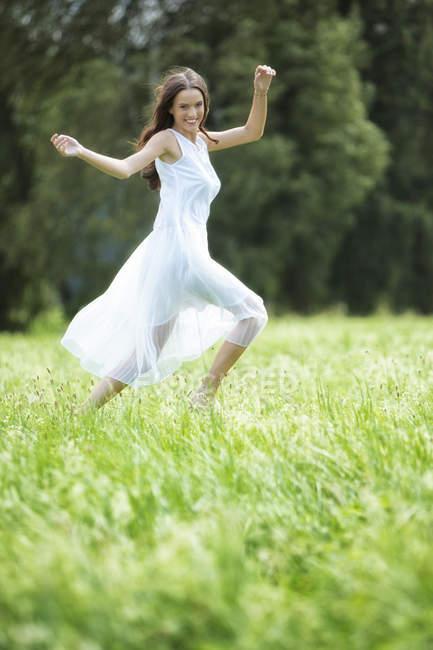 Mujer feliz con vestido blanco de verano en un prado - foto de stock
