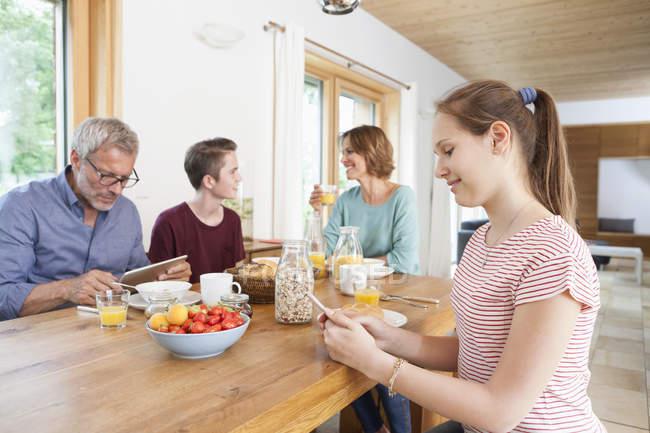 Семья с помощью портативных устройств во время завтрака на дому — стоковое фото