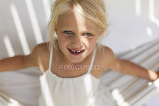 Porträt eines lächelnden kleinen Mädchens mit Zahnlücke in einer Hängematte — Stockfoto