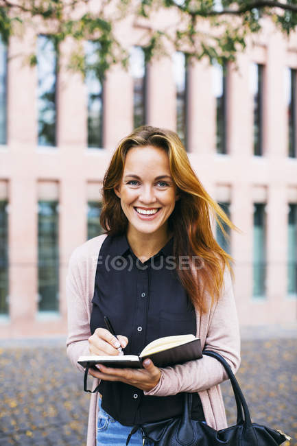 Portrait of smiling young woman standing with notebook — Stock Photo