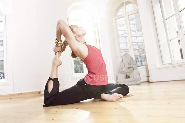 Женщина в позе йоги растягивается — стоковое фото
