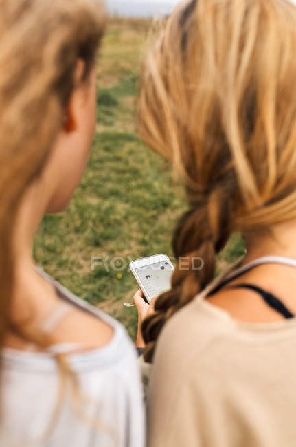 Close-up of two teenage girls sharing smartphone — Stock Photo