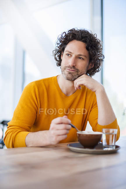 Portrait d'homme songeur avec tasse de cappuccino — Photo de stock