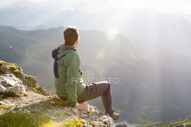 Escursionista seduto in cima godendo il tramonto — Foto stock
