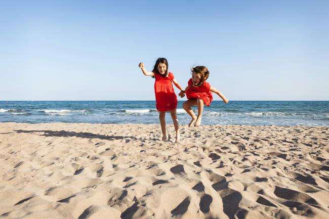Due sorelline che saltano insieme sulla spiaggia — Foto stock