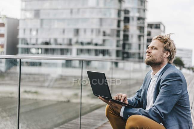 Бизнесмен, сидящий на мосту с ноутбуком — стоковое фото