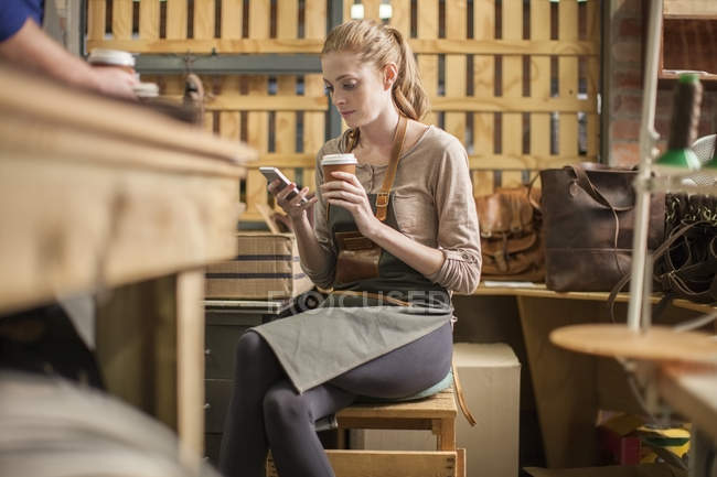 Young woman having a break in leather workshop — Stock Photo