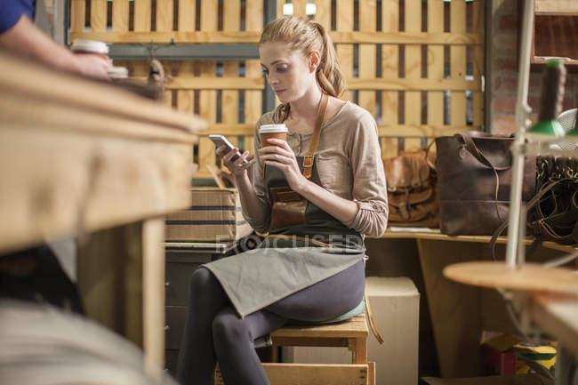 Jeune femme ayant une pause dans l'atelier du cuir — Photo de stock