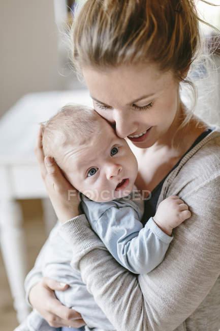 Mère embrassant avec bébé garçon à la maison — Photo de stock