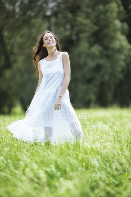 Happy woman wearing white summer dress standing on a meadow — Stock Photo