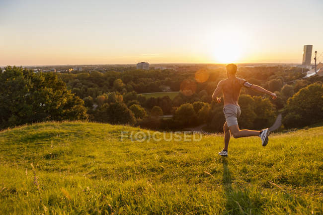 Shirtless man running on meadow in park at sunset — Stock Photo