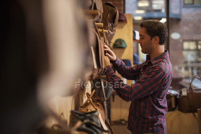 Man in shop exmining leather bags — Stock Photo