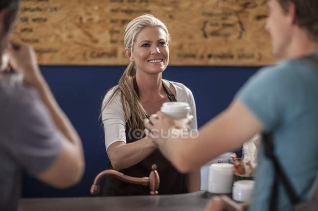 Woman in a cafe handing over disposable coffee cup — Stock Photo