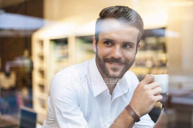 Uomo d'affari sorridente che tiene una tazza di caffè dietro il vetro della finestra nel caffè — Foto stock