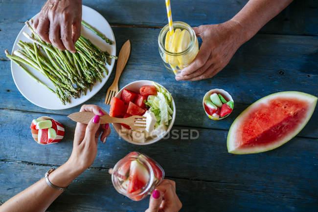 Manos masculinas y femeninas comiendo ensalada, sandía, limonada, espárragos y dulces sobre mesa de madera - foto de stock