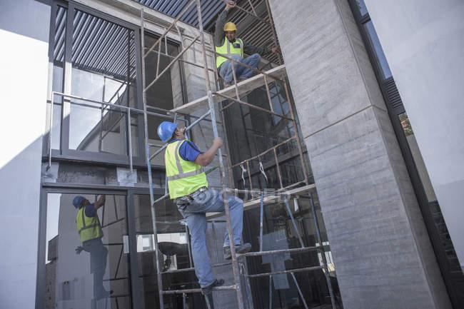 Deux travailleurs de la construction sur des échafaudages travaillant sur chantier — Photo de stock