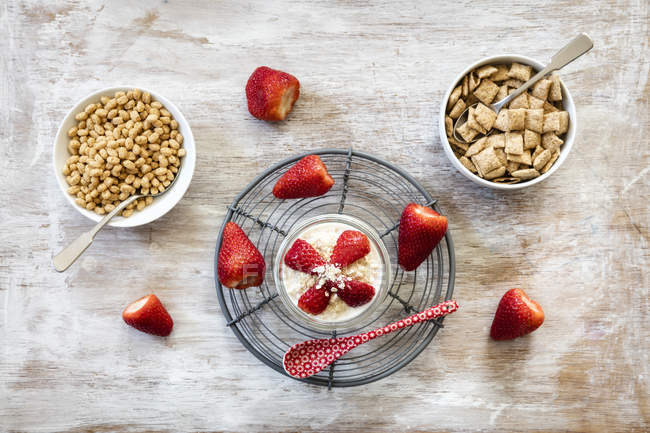 Bowls of whole meal oat cushions and oatmeal flakes, strawberries and glass of porridge — Stock Photo
