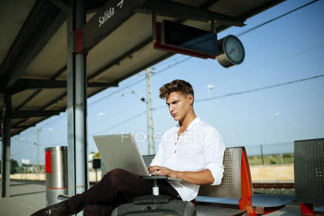 Jeune homme utilisant un ordinateur portable — Photo de stock