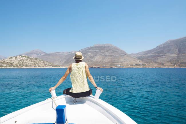Grèce, un homme assis sur la proue d'un bateau à l'île d'Amorgos — Photo de stock