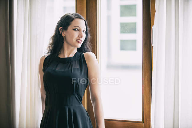 Dark-haired young woman wearing black dress — Stock Photo
