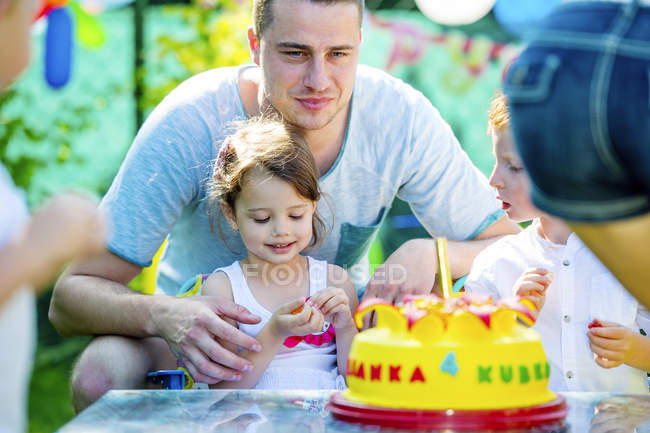 Children celebrating birthday party in the garden with friends and family — Stock Photo
