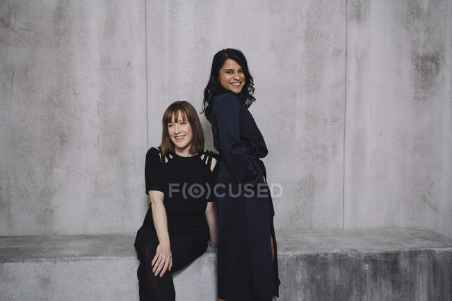 Female Indian and caucasian woman posing against grey wall — Stock Photo