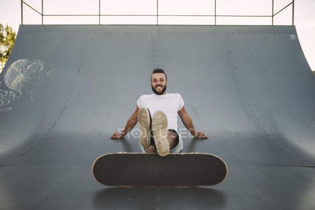 Lächelnde Skateboarder sitzen auf Rampe — Stockfoto