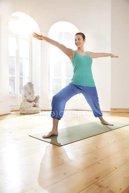 Woman in sunny yoga studio holding Virabhadrasana pose — Stock Photo