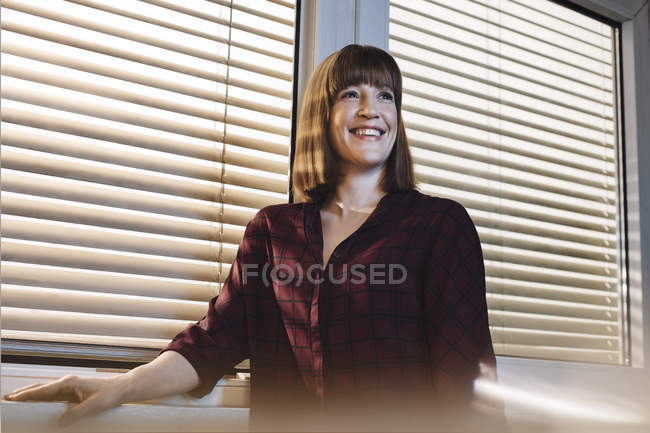 Portrait of smiling woman in front of window — Stock Photo