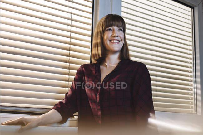 Портрет усміхається жінка перед вікном — стокове фото