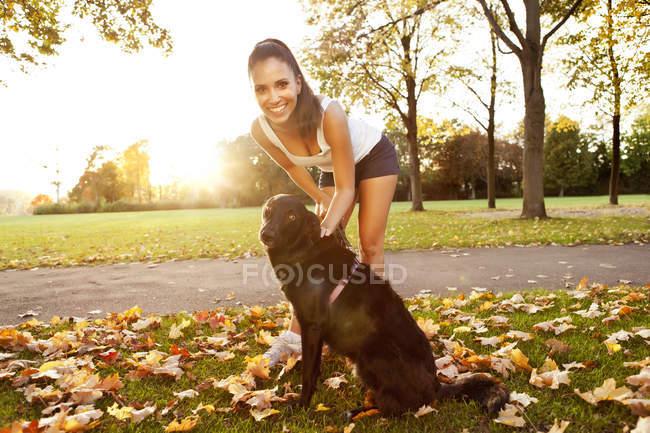 Mulher em um passeio com seu cão no outono — Fotografia de Stock