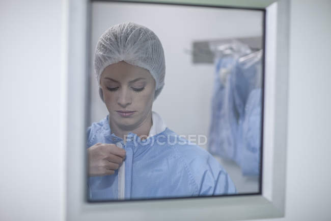 Woman behind glass pane putting on sterile protective clothing — Stock Photo