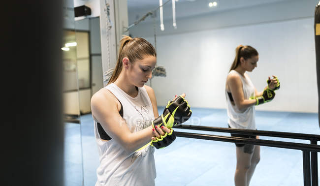 Young woman in gym putting on boxing gloves — Stock Photo