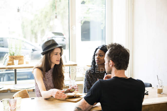 Friends meeting in cafe, eating and having fun — Stock Photo