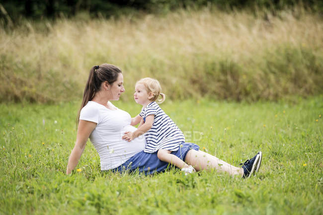 Pregnant woman sitting in grass with little daughter touching mother's belly — Stock Photo