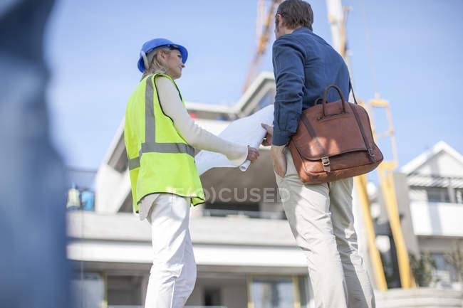Чоловік і жінка, дивлячись на план будівництва — стокове фото