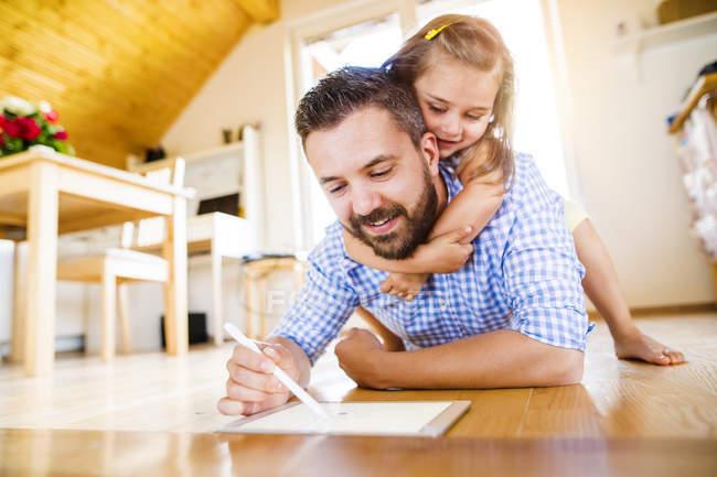 Отец и дочь лежат на полу, рисуют на цифровой табличке — стоковое фото