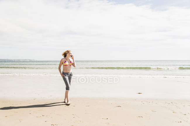 Teenage girl on cell phone walking on the beach — Stock Photo
