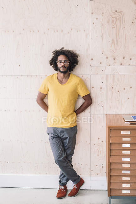Man leaning against wooden wall — Stock Photo