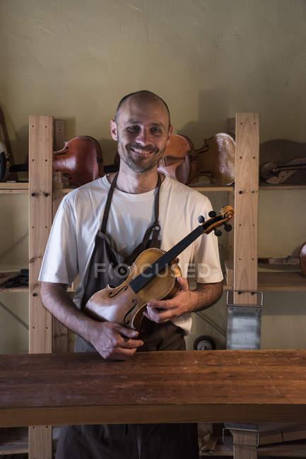 Улыбающийся Лютер держит скрипку в своей мастерской — стоковое фото